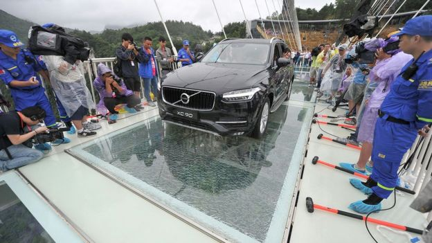 Driving car on glass bridge as part of safety test. - AP